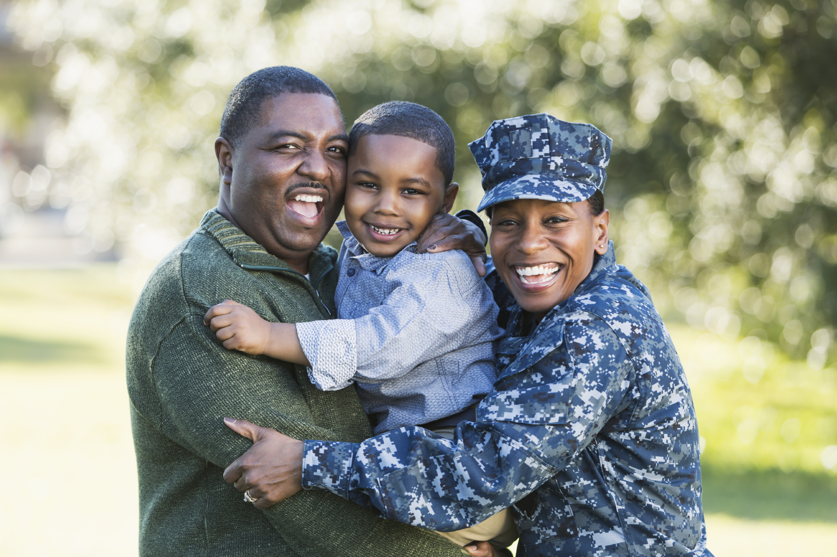 A military homecoming. Portrait of an African American woman wearing navy camouflage uniform standing outdoors with her family. Her husband is holding their 5 year old son who is in the middle between his parents, smiling at the camera. The main focus is on the woman.