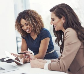 spouseforce image of two women looking at a laptop