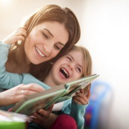 Mother and daughter reading a book and laughing